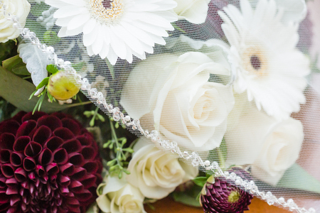 Bridal veil partially covers wedding flowers. Bouquet made up of white roses, white gerberas, and roses Reklamní fotografie - 115939177