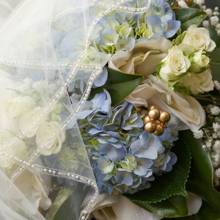 hydrangea, roses, Gypsophila babys breath wedding day bouquet flowers partially covered by veil.