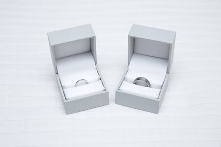 Two ring boxes containing wedding bands for bride and groom, platinum and tungsten silver colored rings for wedding day.