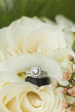 Close up macro of bridal diamond wedding band, grooms band, and engagement ring placed in brides floral bouquet Reklamní fotografie