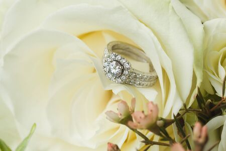 Close up macro of bridal diamond wedding band and engagement ring placed in brides floral bouquet