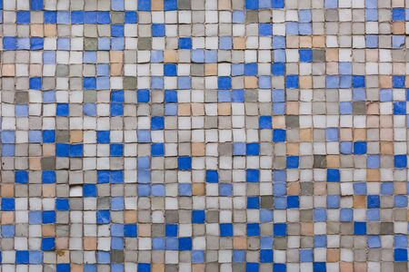 Imperfect wall of mosaic tiles blue and neutral colors, old and worn. Stock Photo