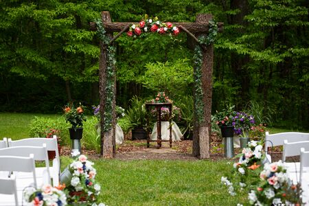Outdoor summer wedding venue path before the ceremony setup with flowers and wooden archway