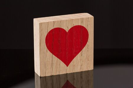 One red heart block tile on black background with reflection. Love concept.