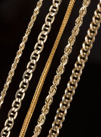 Variety of five gold necklaces close up showing detail of different chains and styles. Black background