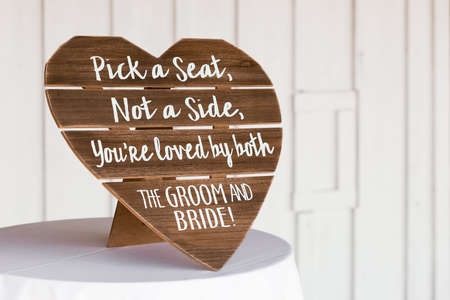 Shot of ceremony signage, pick a seat either side on a wedding day with a blurred background Stock Photo