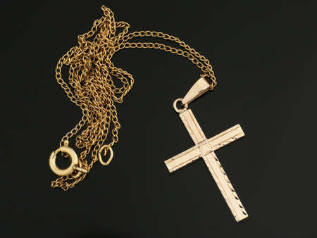 One shiny gold cross pendant on golden chain necklace. Religious jewelry. Christianity.