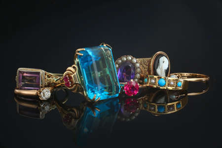 Pile of vintage rings of different color gemstones and diamonds on black reflective background Stock Photo