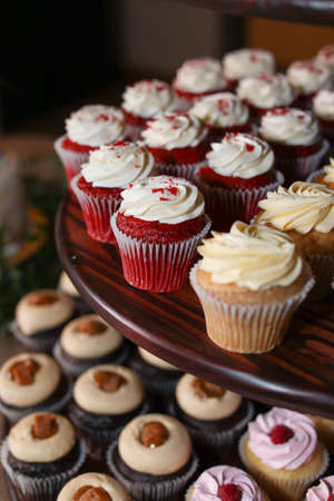 Multiple flavors of gourmet cupcakes on display stand at wedding reception event Stock Photo