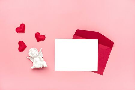 red envelope, white writing paper, cupid, hearts on pink background Happy Valentines day concept, declaration of love Top view Flat lay Holiday Card Copy space Mock up