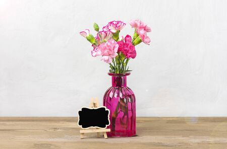 Bouquet of small colored pink carnations in vase, frame on wooden background and grey wall Hello spring, seasonal concept Mock up Place for text Holiday card. Banque d'images - 140627842