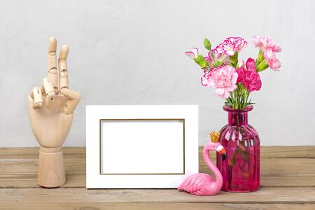 Small colored pink carnations in vase, white photo frame, figure of flamingo, wooden hand on wooden table and grey wall Hello spring, seasonal concept Mock up Place for text.