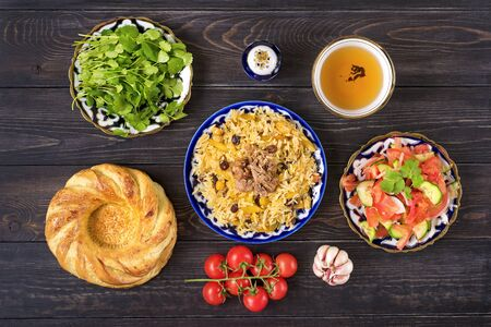National Uzbek pilaf with meat, achichuk salad of tomato, cucumber, onion in plate with traditional pattern, cilantro, cherry tomatoes, garlicbread tortilla - patir on dark wooden table Top view.
