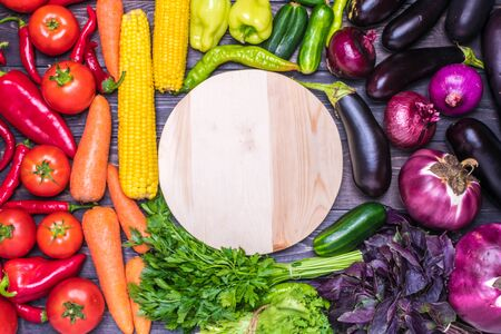 tabletop arrangement of a variety of fresh fruits and vegetables sorted by colors - pepper, tomato, corn, carrot, green salad, cilantro, eggplant, cucumber, basil, dill, onion. Healthy food concept.
