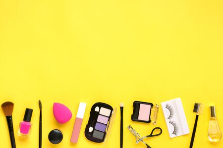 Set of professional decorative cosmetics, makeup tools and accessory of trendy pink color isolated on yellow background Flat lay Top view.