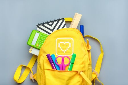 Back to school, education concept. Yellow backpack with school supplies - notebook, pens, ruler, calculator, scissors isolated on gray background. Top view. Copy space Flat lay composition Banner. Archivio Fotografico