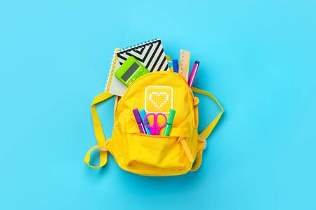 Back to school, education concept. Yellow backpack with school supplies - notebook, pens, ruler, calculator, scissors isolated on blue background. Top view. Copy space Flat lay composition Banner.