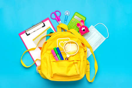 Back to school, education concept Yellow backpack with school supplies, protective medical mask, calculator, scissors isolated on blue background. Top view Copy space Flat lay. Reklamní fotografie