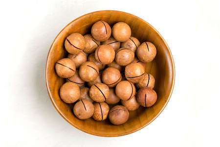 natural organic macadamia nuts in wooden bowl on gray concrete background Flat lay Top view Healthy snack Nuts with essential oil rich in vitamins B, PP, lot of fats and high in calories Superfood.