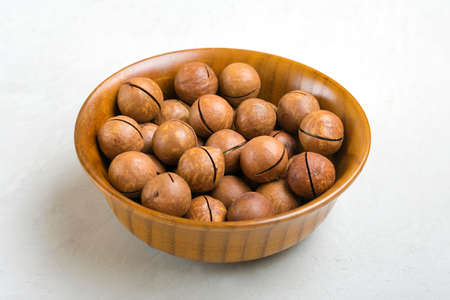 natural organic macadamia nuts in wooden bowl on gray concrete background Flat lay Top view Healthy snack Nuts with essential oil rich in vitamins B, PP, lot of fats and high in calories Superfood. Imagens
