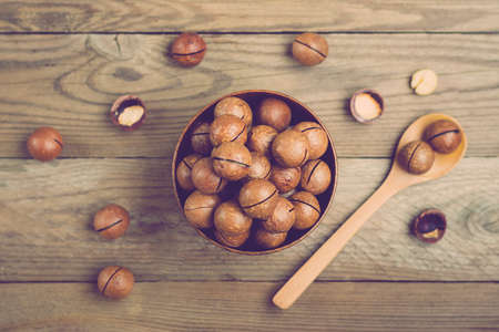 natural organic macadamia nuts in bowl on wooden table Flat lay Top view Healthy snack Nuts contain essential oil rich in vitamins B and PP, lot of fats and high in calories. Superfood.