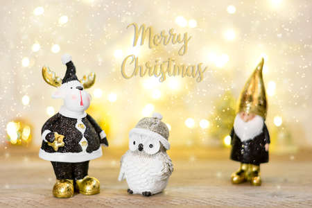 gnome, owl, moose decorated with sequin in black, golden color on bokeh background. Happy New Year, Merry Christmas concept Holiday card Flat lay Top view Scandinavian style. Stock Photo