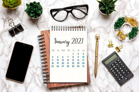 Open Calendar January 2021, glasses, cup of coffee, pen, smartphone, succulents on marble table Top view Flat lay Education, goals, resolutions, plan, small owner business concept Home workplace.