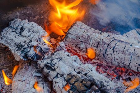 Burning coals from logs on the fire. The wind blows the burning fire
