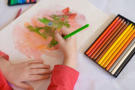 Children's hands on a white table drawing Christmas tree with colored pencils. Drawing a Christmas tree with pencils