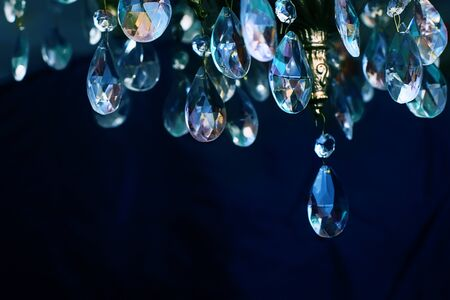 Crystal chandelier close-up. Cold and warm reflections on the edges of the crystal. Dark background Zdjęcie Seryjne
