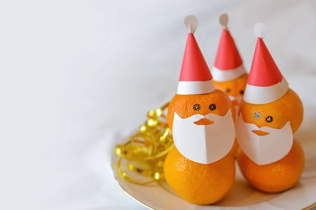 Christmas tangerines in the form of Santa Claus. Christmas tangerines in the form of a Christmas character