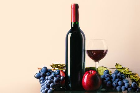 Wine. Glass and bottle of red wine with grapes and apples. Red wine on a light background.