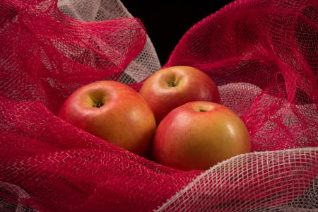 things that go together: Red apples on a red background in a photographic studio