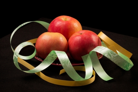 things that go together: Red apples on a black background with color ribbons Stock Photo