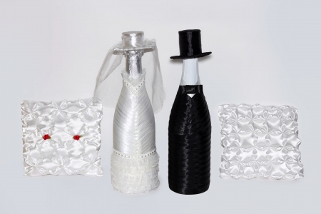 Wedding set the dressed bottles, the groom and the bride and pillows for rings on a white background photo