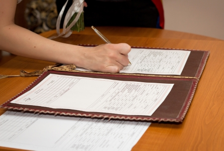 marriage certificate: Photo of bride signing the marriage certificate  Stock Photo