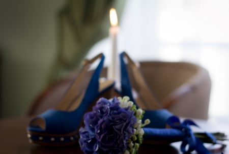 Wedding flowers, shoes and burning candle photo
