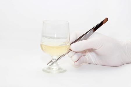 De hand, in een steriele handschoen, houdt pincet een glas
