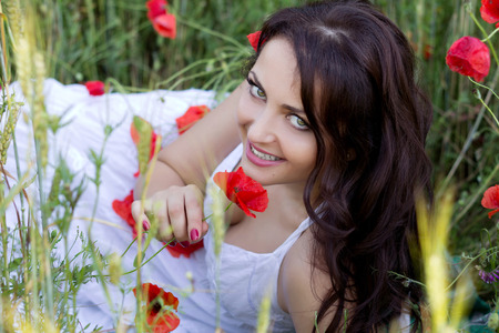 Portrait of the beautiful smiling girl in the poppy field photo
