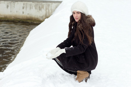 Cheerful young woman standing outside in snow in beanie and white gloves on the bank of the lake holds in hand snow photo