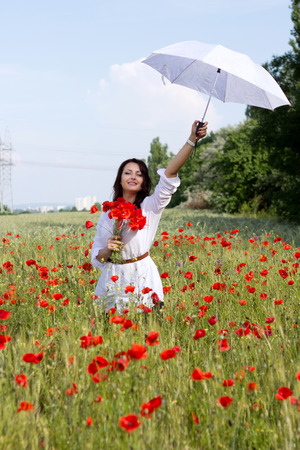 Portrait of the beautiful smiling girl in the poppy field with an umbrella photo