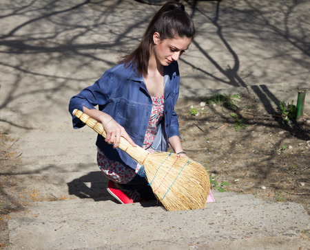 sweeps: Portrait of young woman sweeps with a sweeper garbage outdoor