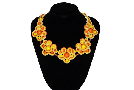artists dummy: Yellow-orange beautiful necklace on a rack on white background Stock Photo