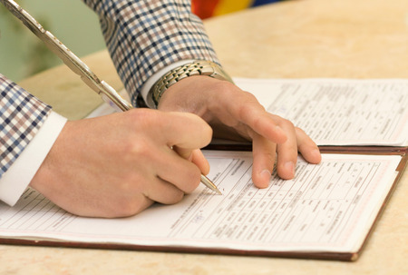 shorthand: Photo of groom signing the marriage certificate