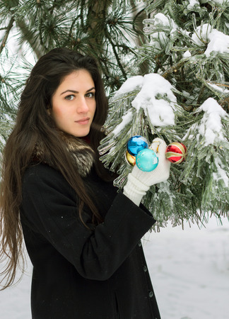 decorates: Young brunette girl decorates a fir tree with toys outdoor
