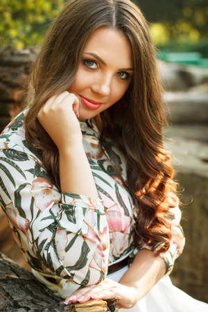 greet eyes: Portrait of smiling beautiful brunette girl with blue eyes outdoors