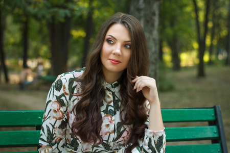 greet eyes: Beautiful brunette girl poses on bench in park outdoors