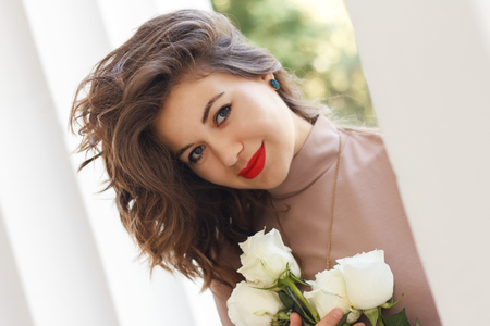 portrait of beautiful woman with a bouquet of roses standing near ancient colons