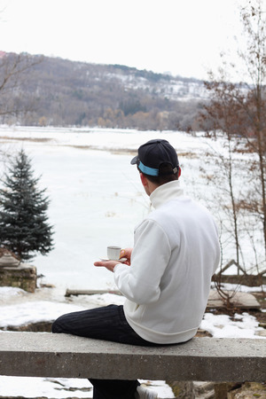 Man has coffee in winter time in fresh air and looks at the frozen lake Stock Photo