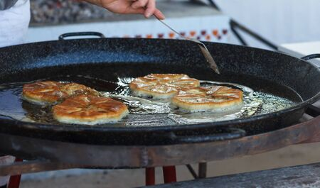 Cook roasts flour pastries in a large pan with butter outdoor